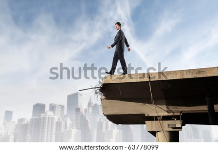 Businessman walking towards the void on a bridge - stock photo