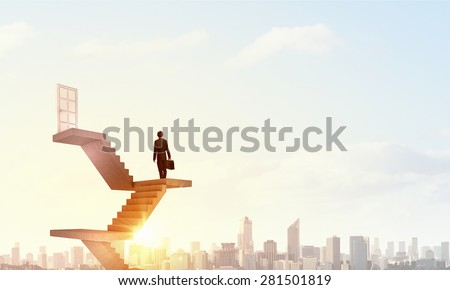 Businessman walking up staircase to door in sky - stock photo