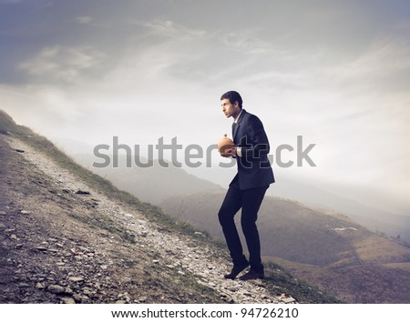 Businessman walking uphill and carrying a money box