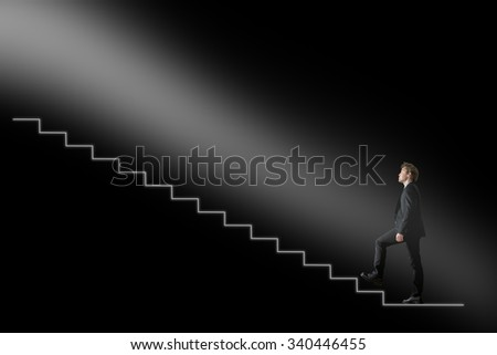 Businessman walking upwards towards the light on conceptual stairway over black background. Conceptual of business development or hope and belief. - stock photo