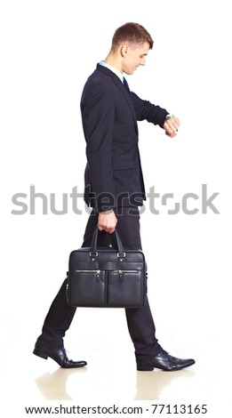 Businessman walking with bag and watching the time Isolated over white background