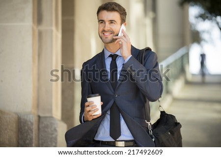 Businessman walking with coffee and briefcase on the phone - stock photo