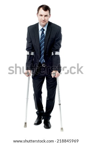 Businessman walking with crutches isolated on white - stock photo