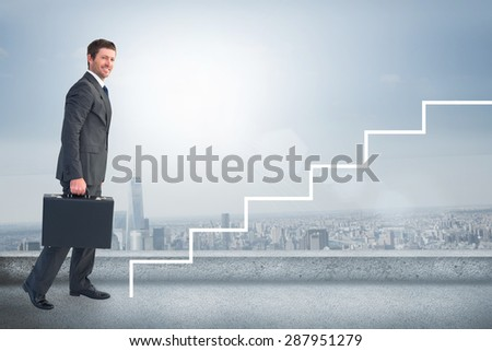 Businessman walking with his briefcase against cityscape