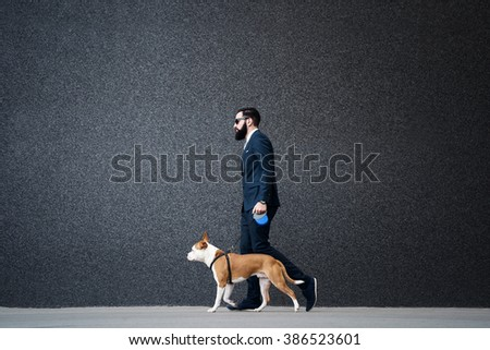 Businessman walking with his dog. - stock photo