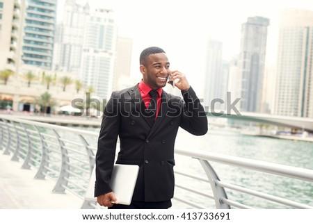 Businessman walking with laptop and talking on smart phone at Dubai Marina. - stock photo