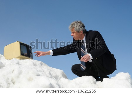 Businessman watching TV on a mountain