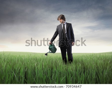 Businessman watering a green meadow - stock photo