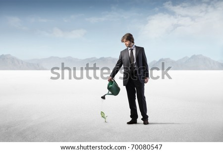Businessman watering a plant in a desert - stock photo