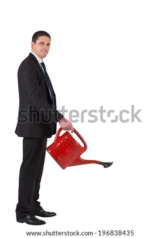Businessman watering with red can and smiling at camera on white background - stock photo