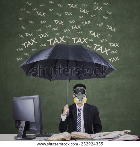 Businessman wearing a gas mask and umbrella to protect him from tax - stock photo