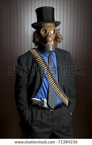 Businessman wearing a gasmask and a bullet belt with a gun tucked into his pants - stock photo