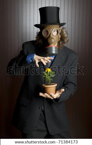 Businessman wearing a gasmask holding a flower - stock photo