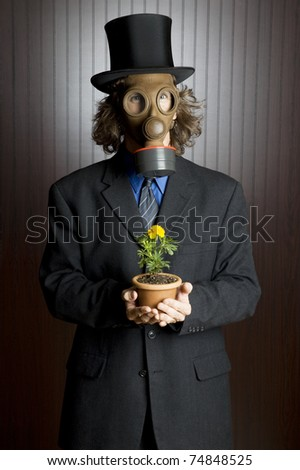 Businessman wearing a gasmask holding a flower