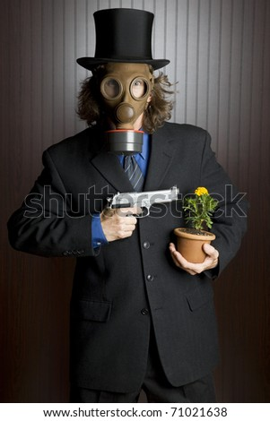 Businessman wearing a gasmask holding a gun to a flower - stock photo