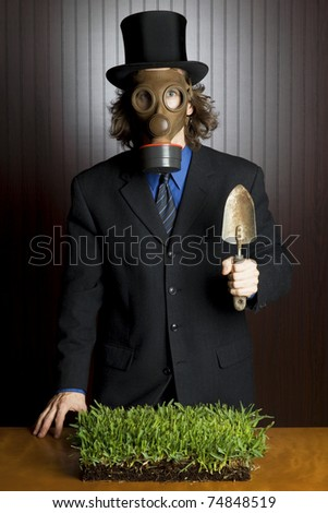 Businessman wearing a gasmask holding a potting shovel standing over a patch of grass - stock photo