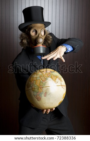 Businessman wearing a gasmask holding an earth globe - stock photo