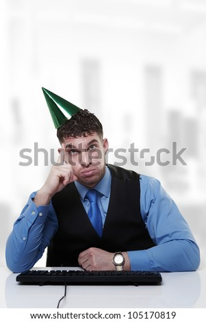 businessman wearing a party hat sitting at his desk