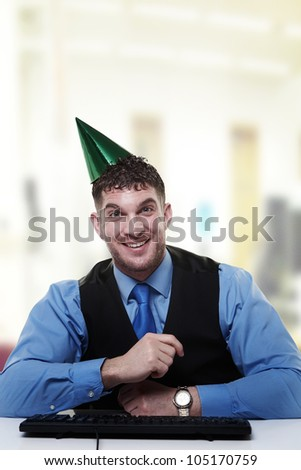 businessman wearing a party hat sitting at his desk looking very happy