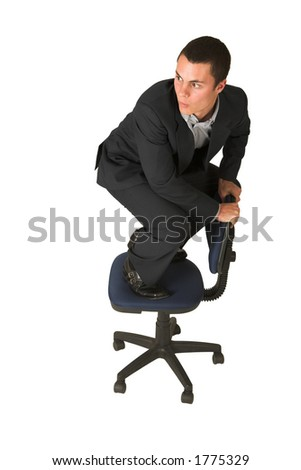 Businessman wearing a suit and a grey shirt.  Making a stunt on an office chair