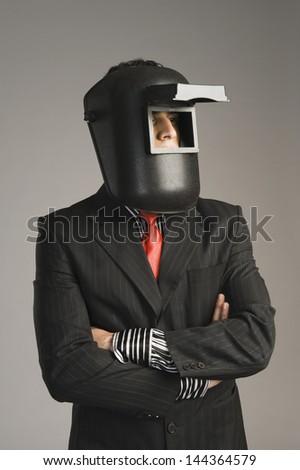 Businessman wearing a welding mask - stock photo