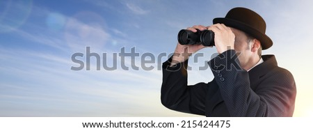 Businessman wearing bowler hat looking through binoculars concept for finance, future investment and searching