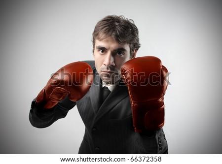 Businessman wearing boxer gloves - stock photo