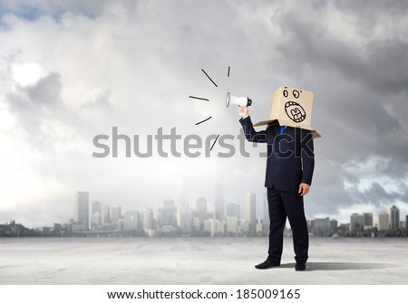 Businessman wearing carton box on head and screaming in to megaphone - stock photo