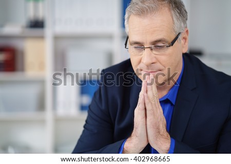 Businessman wearing eyeglasses deep in thought with his eyes closed and hands clasped as he seeks an answer to a problem - stock photo