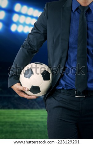 Businessman wearing formal suit and holding a soccer ball, symbolizing business competition - stock photo