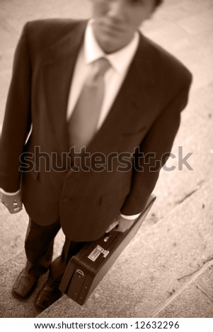 Businessman wearing full suit standing carrying briefcase - stock photo