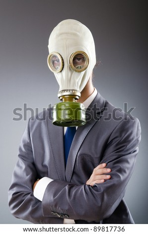 Businessman wearing gas mask - stock photo
