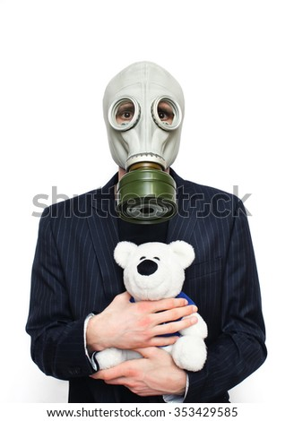 Businessman wearing gas mask with teddybear isolated on white  - stock photo