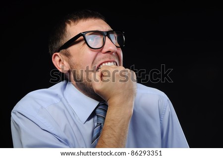 Businessman wearing glasses in horror watching stocks fall on black background, concept - stock photo