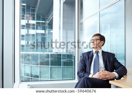 Businessman wearing glasses on the background of a large window in the office - stock photo