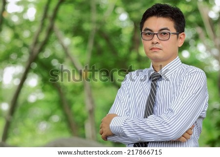Businessman wearing glasses standing arms crossed in park - stock photo