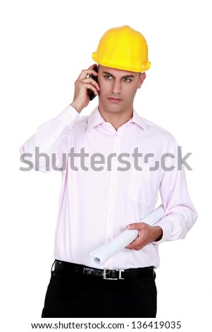 businessman wearing helmet and talking on the phone