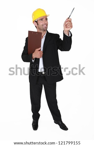 businessman wearing helmet pointing with a pen