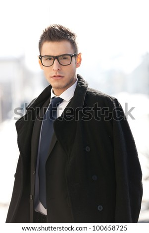 Businessman wearing suit , coat and glasses, looking to the camera - outdoor picture - stock photo