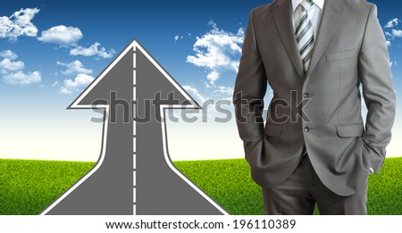 Businessman wearing suit. Road climbs up. Field of grass and sky as background - stock photo