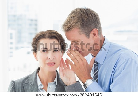 Businessman whispering something to his colleague in an office - stock photo