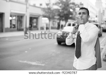 Businessman whistling to a taxi cab - stock photo