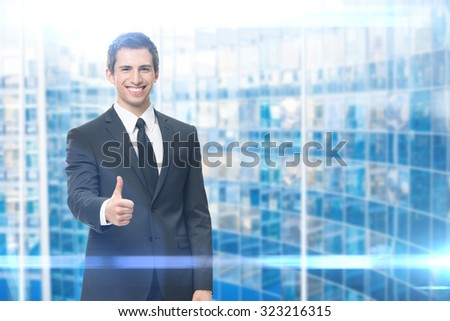 Businessman who thumbs up on blue background. Concept of leadership and success - stock photo
