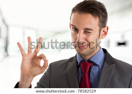 Businessman winking at you while doing the ok sign - stock photo