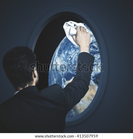 Businessman wiping dark spaceship window with earth view. Element of this image furnished by NASA - stock photo