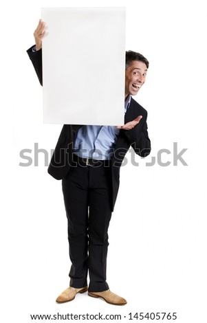 Businessman with a blank white sign peering around the side with a cheeky grin endorsing the text or advertisement to be placed on the copyspace - stock photo