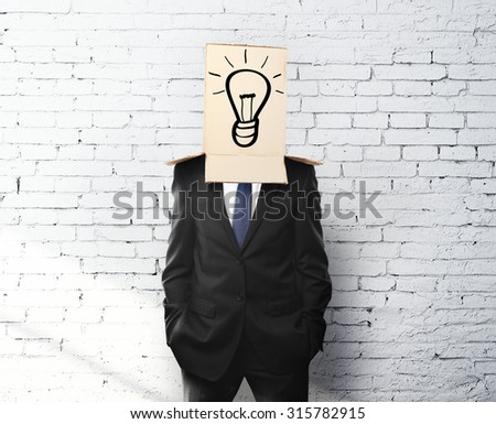 businessman with a box on head and drawing lamp - stock photo