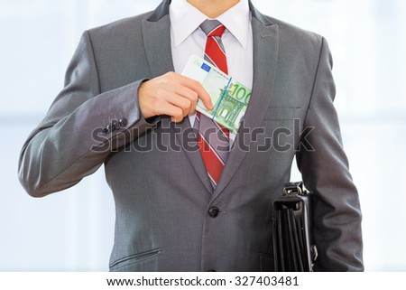 Businessman with a briefcase putting bribe money into his suit pocket. - stock photo