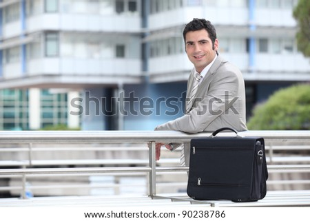 Businessman with a briefcase standing in an urban environment - stock photo
