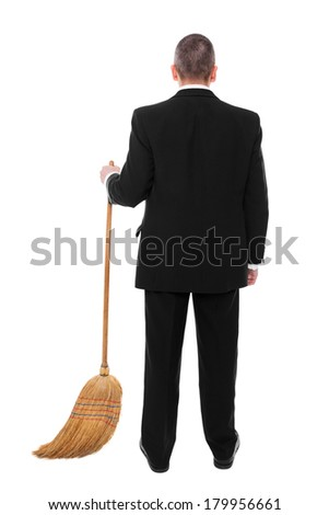 Businessman with a broom is cleaning the ground - stock photo